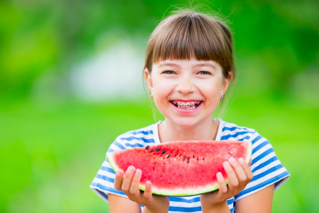 girl with braces eating a watermelon